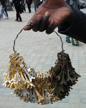 Seller holding huge wire-ring with many Eiffel-tower-key-fobs.