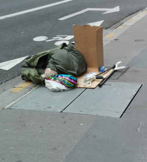 Homeless person sleeping on the street blocking the wind using a paper box.
